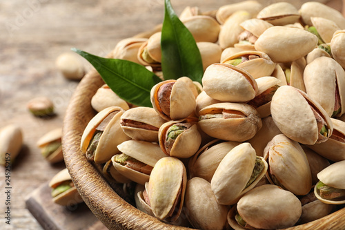 Organic pistachio nuts in bowl on wooden table, closeup