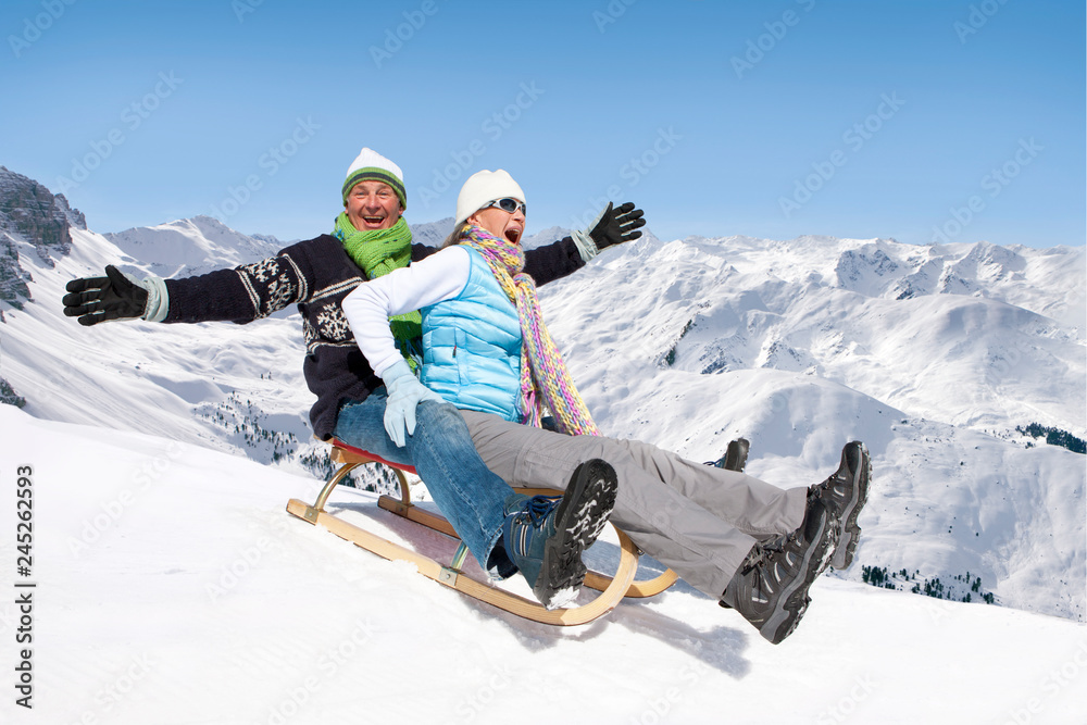 Fototapety, obrazy: Laughing senior couple on winter vacation riding sled down mountain smiling at camera