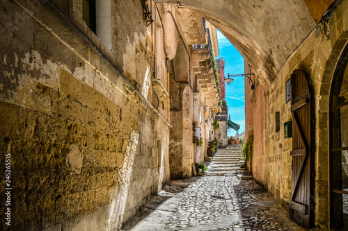 Fototapeten Schmale Gasse A covered alley leads to a cafe and piazza in the ancient city of Matera, Italy