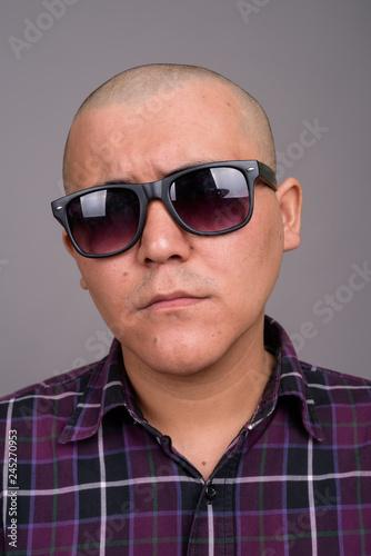 Obraz na plátně Young bald Asian businessman against gray background