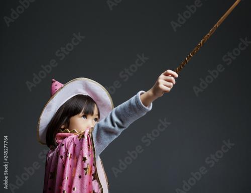 Fotografie, Obraz  Asian little girl playing magic in the studio