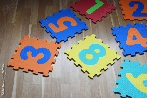 Fotografie, Tablou  Numbers puzzle pieces different vibrant color on brown wooden texture laminate floor indoors