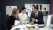 Blurred view, businessman gives instructions to girls managers, teamwork in office interior.