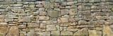 Fototapeta Kamienie - Panorama einer groben, sehr alten Natursteinmauer aus unterschiedlich großen Steinen