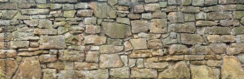 Photo Panorama einer groben, sehr alten Natursteinmauer aus unterschiedlich großen Ste