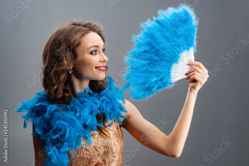 Photo  Beautiful young girl in a blue boa holding a fan of feathers in his hand