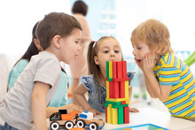 Little Kids Build Wooden Toys At Home Or Daycare. Emotional Kids Playing With Color Blocks. Educational Toys For Preschool And Kindergarten Children.