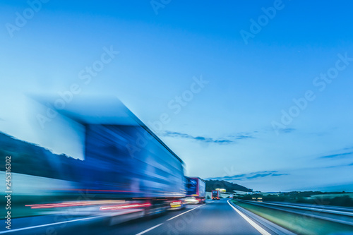 Fotobehang Nacht snelweg Background photograph of a highway. Truck on a motorway, motion blur, light trails. Evening or night shot of trucks doing logistics and transportation on a highway.