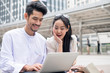 Young man with asian girlfriend playing laptop are happy smiling