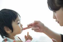 子供の口に付いた汚れをとる母親
