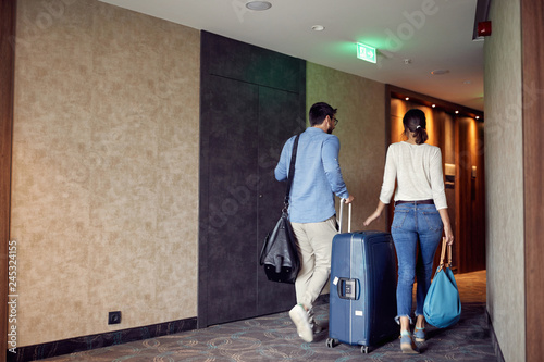 Fotografie, Obraz  Couple arriving at hotel lobby with suitcase.