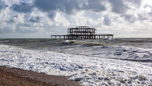 Landscape View Of Beach And Sea With Big Waves. Remains Of Old Pier In The Background. Brighton, United Kingdom.