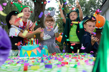 Kids Enjoying The Confetti Rain During Birthday Dressing Up Party In The Garden