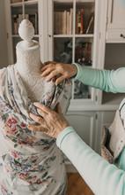 Dressmaker Adjusting Apparel On Mannequin