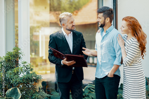 Smiling man and woman talking with financial advisor about house loan Wallpaper Mural