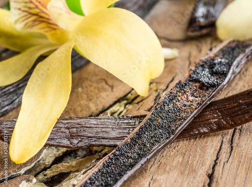 Tuinposter Kruiderij Dried vanilla fruits and vanilla orchid on wooden table.