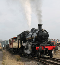 A Vintage Steam Engine Pulling A Goods Freight Train.