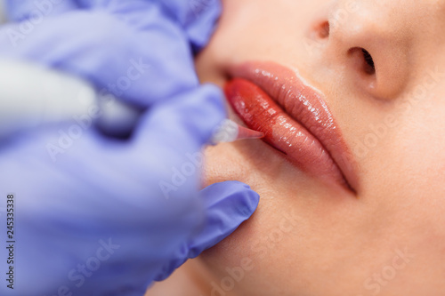 Obraz Young woman having permanent makeup on lips in beautician salon. Close up - fototapety do salonu