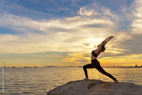Fotografía  Silhouette  healthy woman lifestyle exercising vital meditate and practicing yoga outdoors on the rock at beach sunset and twilight time, city night background