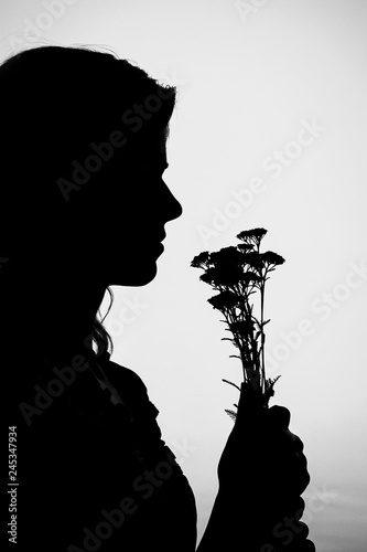 Recess Fitting Military Happy girl with a bouquet silhouette on nature in the park sunset