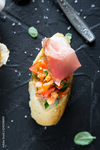 Bruschetta with prosciutto, tomatoes and basil