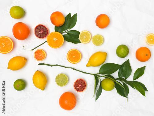 Obraz na plátně  many different fresh citrus fruits on white crumpled paper background