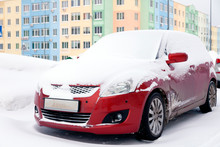 Closeup Of Small Red Dirty Car Covered With Snow Stands On Background Colored House. Front View. Concept Snowy Weather, Snowfall, Bad Northern Weather Conditions, Low Battery, Severe Frost