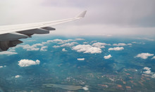 Aerial View. Wing Of An Airplane Flying Above The Clouds