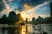 Silhouette Of Cormorant Fisherman Using Net On The Ancient Bamboo Boat