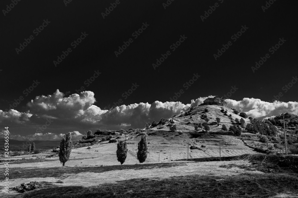 Black and white countryside landscape with small gentle clouds