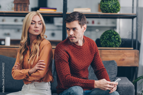Fotografiet young man holding smartphone and looking at confident girlfriend sitting with cr