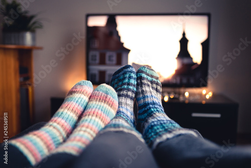 Fotomural Couple with socks and woolen stockings watching movies or series on tv in winter