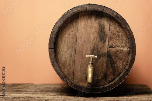 Vászonkép Wooden barrel with tap and worn old table of wood.