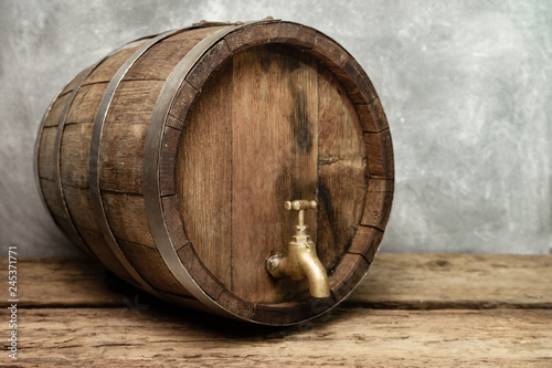 Fotografia Wooden barrel with tap and worn old table of wood.