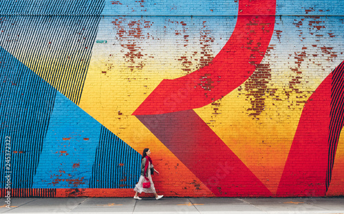Young girl walking by the wall with graffiti - 245372322