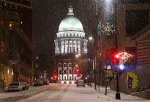 Snowy Storm In A City Background. Weather Alert Concept. Blizzard Night Downtown Cityscape With Glowing Capitol Building And Baked Cars Along Street. Midwest USA, Wisconsin, Madison.
