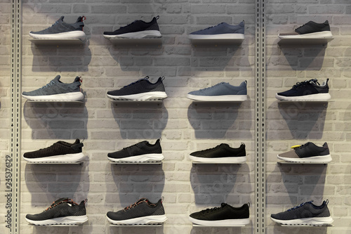Photo Shop display of unbranded modern new stylish sneakers running shoes for men on brick wall background texture