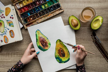 Top View Of Female Hands Drawing Avocados With Watercolor Paints And Paintbrush On Wooden Table