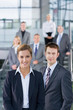 Team of businessmen and businesswomen standing on stairs in office smiling at camera