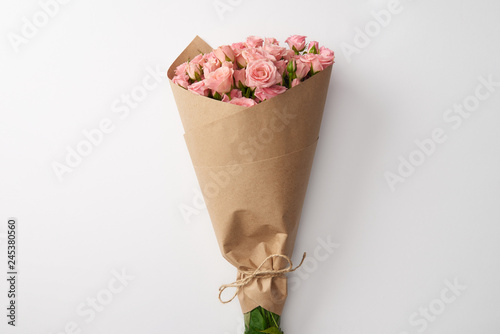 Photo bouquet of beautiful pink roses wrapped in craft paper on grey