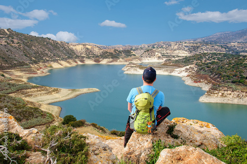 Photo Stands Cyprus tourist with backpack looks at a beautiful reservoir from a viewing platform in Cyprus
