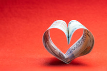 US 100 Dollar Bill In The Shape Of A Heart On A Red Background. Concept Of Money, Love And A Gift For Valentine's Day. Copy Space.