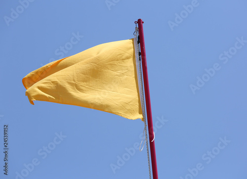 yellow flag waving in the blue sky as a warning Canvas Print