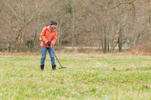 A Young Woman Uses A Detector To Find Different Metal Under The Ground