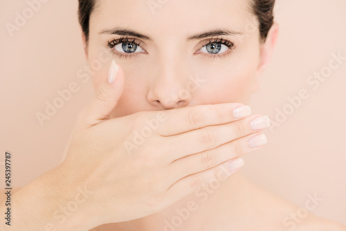 Fototapeta  Studio shot of young woman with hand covering mouth looking at camera