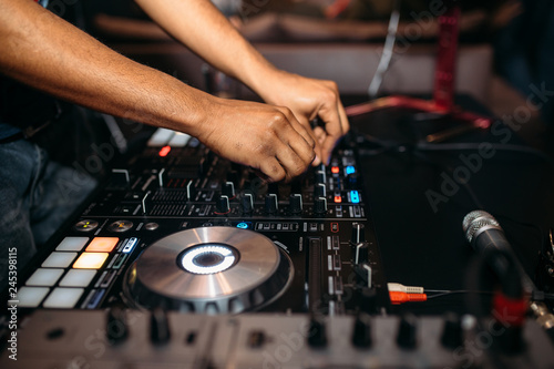 Fotografie, Obraz  Close up of DJ's hand playing music at turntable on a party festival - Portrait