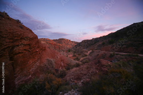 Spoed Foto op Canvas Bordeaux red rocks canyon with red and blue sunset