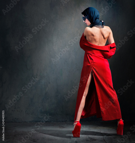 Carta da parati Fashion photo of beautiful woman with naked back in headscarf, red coat and shoe