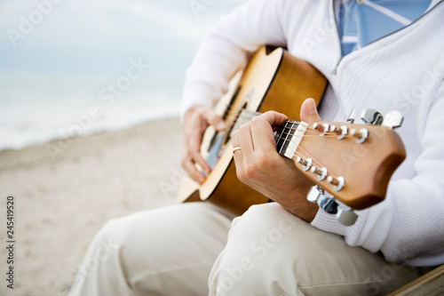 Fotografie, Obraz  Detail of man playing acoustic guitar on beach