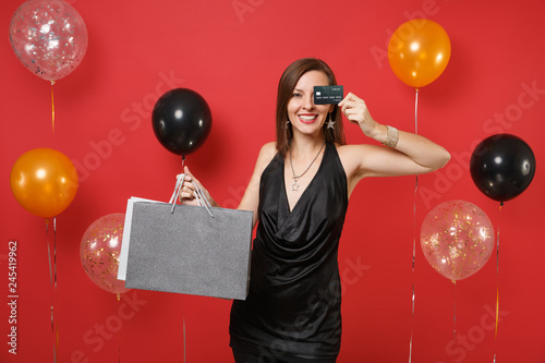 Photo  Pretty girl in black dress covering eye with credit card holding packages bags with purchases after shopping on bright red background air balloon